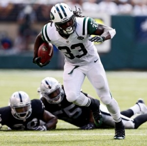 Chris Ivory #33 of the New York Jets rushes after evading tackle attempts by T.J. Carrie #38 and Sio Moore #55 of the Oakland Raiders during the third quarter of a game at MetLife Stadium on September 7, 2014 in East Rutherford, New Jersey. (Photo by Jeff Zelevansky/Getty Images)