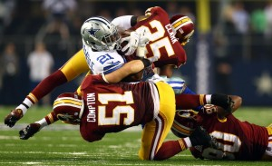 ARLINGTON, TX - OCTOBER 27: Joseph Randle #21 of the Dallas Cowboys is tackled by Everette Brown #51 and Ryan Clark #25 of the Washington Redskins during the second half at AT&T Stadium on October 27, 2014 in Arlington, Texas. (Photo by Ronald Martinez/Getty Images)